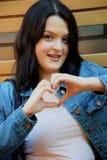 La jeune fille de sourire fait le coeur avec des doigts photos libres de droits
