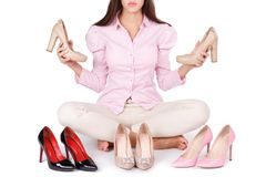 La jeune fille de sourire présente quatre paires modernes de chaussures à talons hauts d'isolement sur un fond blanc Photographie stock