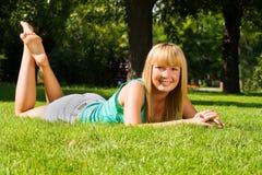 La jeune fille de sourire se trouve sur l'herbe image stock