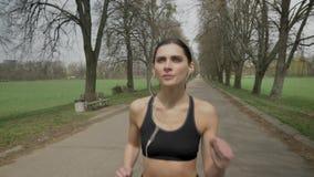 La jeune fille de sport court avec des écouteurs en parc en été, mode de vie sain, conception de sport banque de vidéos
