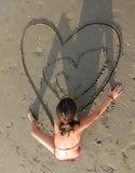 La jeune fille dessine beaucoup de coeurs sur la plage Photo libre de droits