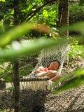 La jeune fille dort dans l'hamac dans le jardin Images libres de droits