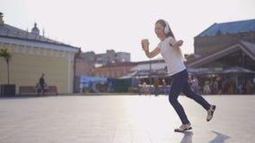 La jeune fille drôle a l'amusement marchant autour de la ville et de la danse femme écoutant la musique dans de grands écouteurs  clips vidéos