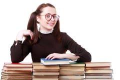 La jeune fille drôle s'asseyant au bureau avec des livres réservent Photos libres de droits