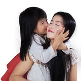La jeune fille embrassent sa maman dans le studio Photographie stock libre de droits