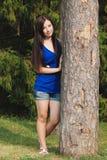 La jeune fille en bref s'est penchée contre un arbre en parc Image stock