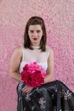 La jeune fille en satin blanc pur de dessus et de vintage bordent se reposer tenant le bouquet i images libres de droits