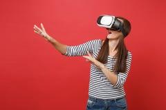 La jeune fille en verres de réalité virtuelle touchent quelque chose comme le bouton ON de poussée se dirigeant à flotter l'écran photo stock