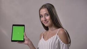 La jeune fille enthousiaste est tapante et montrante l'écran vert du comprimé, observant à l'appareil-photo, souriant, concept de clips vidéos