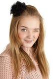 La jeune fille espiègle cligne de l'oeil sur le fond blanc Photographie stock libre de droits