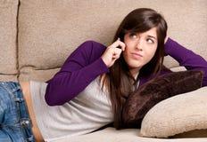La jeune fille est concernée parler par la mauvaise nouvelle de téléphone se trouvant sur le divan Photos stock
