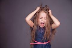 La jeune fille est screeming et tenante ses cheveux Image libre de droits
