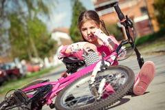 La jeune fille est tombée du vélo en parc photographie stock