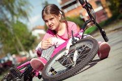 La jeune fille est tombée du vélo en parc photos libres de droits