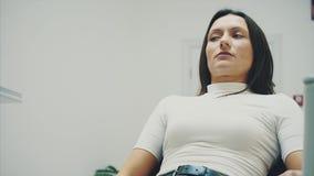 La jeune fille est venue chez le dentiste During cette fois où il se repose dans la chaise d'un dentiste rouge La crainte pour de banque de vidéos