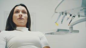La jeune fille est venue chez le dentiste During cette fois où il se repose dans la chaise d'un dentiste rouge La crainte pour de clips vidéos