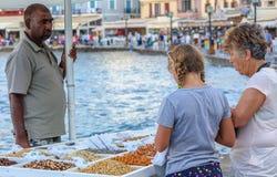 La jeune fille et la dame âgée achètent des écrous de marchand ambulant au vieux port de ville de Chania Photo stock