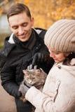 La jeune fille et le type avec le chat en automne se garent photo stock