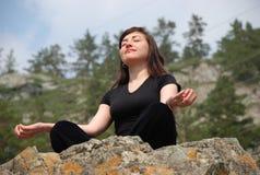 La jeune fille européenne médite en montagnes. Image libre de droits