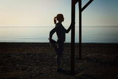 La jeune fille faisant le yoga s'exerce à la plage de mer images stock