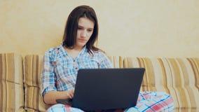 La jeune fille finit son travail sur l'ordinateur portable banque de vidéos