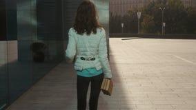La jeune fille futée d'étudiant en verres marche dehors avec des livres dans les mains et les sourires clips vidéos