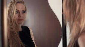 La jeune fille gaie blonde attirante regardant dans le miroir, cheking composent banque de vidéos