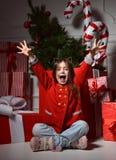 La jeune fille heureuse avec la diffusion augmentée remet Noël smilingnear Photographie stock libre de droits