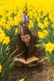 La jeune fille heureuse d'adolescent lit le livre parmi des fleurs Photo libre de droits