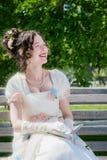 La jeune fille heureuse dans une longue robe blanche de jeune mariée avec un sourire est rea Photographie stock