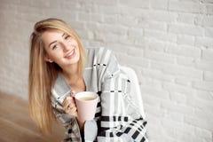 La jeune fille heureuse enveloppée dans une couverture chaude semble heureuse tenant la tasse de thé à l'intérieur photographie stock