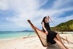 La jeune fille heureuse s'asseyent sur le bateau sur la plage blanche Photos stock