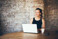 La jeune fille heureuse s'assied dans un café de grenier et cause avec son ami à l'aide de l'ordinateur portable photographie stock