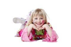 La jeune fille heureuse se trouve sur l'étage et sourit Photographie stock libre de droits