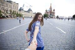 La jeune fille heureuse tire la main de types sur la place rouge à Moscou images stock