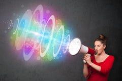 La jeune fille hurle dans un haut-parleur et le faisceau d'énergie coloré sort Photos libres de droits