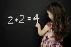 La jeune fille intelligente est restée l'écriture sur un tableau noir Photo stock