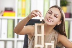 La jeune fille joue avec les briques en bois Photographie stock libre de droits