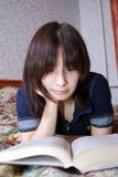 La jeune fille l'adolescent se trouve sur un lit avec le livre Elle était fanatique de la lecture images stock