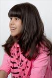 La jeune fille latine avec les cheveux soyeux et a coloré des accolades Image stock