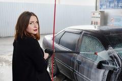 La jeune fille lave la voiture Photos stock