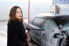 La jeune fille lave la voiture Photo libre de droits