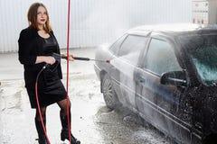 La jeune fille lave la voiture Photographie stock