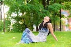 La jeune fille a le reste sur la pelouse Image libre de droits
