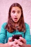 La jeune fille lit le message textuel photo libre de droits