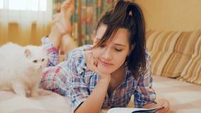 La jeune fille a lu les notes dans le carnet, préparant à l'examen ; chat blanc près de fille banque de vidéos