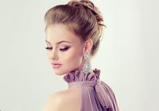 La jeune fille magnifique s'est habillée dans la robe de soirée et le maquillage sensible dessus photo stock