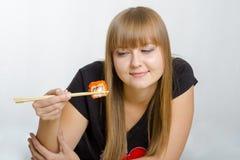 La jeune fille mange les baguettes en bois de petits pains Photographie stock