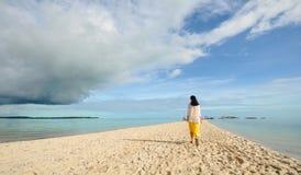 La jeune fille marche sur la longue plage étroite Photos stock