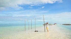 La jeune fille marche sur la longue plage étroite Photos libres de droits
